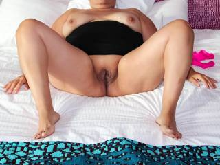 A vacation photo…nude on a resort bed with my legs open wide so you can see my smooth pussy!