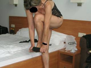 wife dresing for encounter in hotel room..