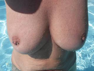 Another pic of my big tits with their pierced nipples, in the swimming pool at home. 