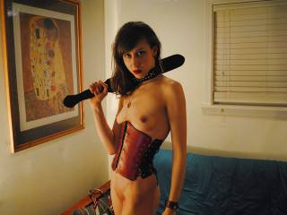 GypsieGirl in a red leather corset and packing a ebony wood paddle both made by ivanhoe