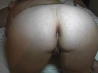 Another closeup of the wife's ass and pussy while she is on a bed in a hotel room sucking a friend