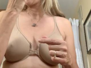 Putting on that shiny red lipstick that drives my man crazy…. Looks like my nipple is trying to drill through my bra - can you tell that I am horny