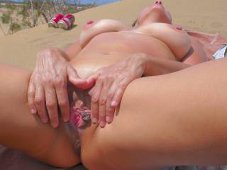 Horny at the beach, spreading her pink to bypasers trying to catch some sun.