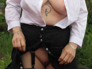 Wearing her stockings and suspenders, her shirt is subtly open to show her tits.
