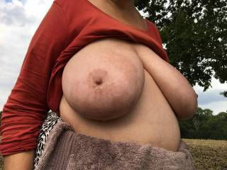 On top of a hill with a tree behind, my friend has oiled her tits - one facing and one sideways, with the nipple against the sky