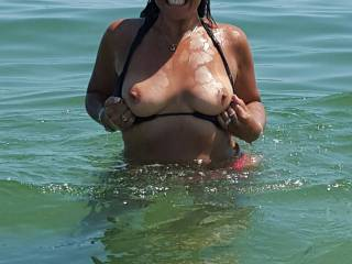 Jungle bum flashing her tits at the beach.  Bukkake time?