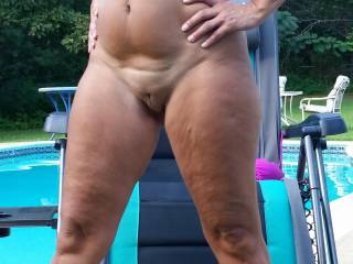 We love getting naked outdoors like this.  Your wife's pussy is very much like my wife.  If I were tehr I'd kneel down in front of he & lap at that pussy whilst fondling her wonderful full tits & nipples - until her knees buckled with orgasm and she collapse into that chair.  Then she coudl suck my cock & swallow my cum - or use my cum as sunblock!  Bet you have some fun fuck sessions in that pool - we do whenever we get access to a private pool.