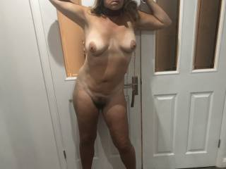 My wife's arms are restrained above her head by a door jam restraint and she's wearing her slut collar. Her pussy was soaking wet