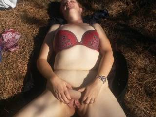 Outside laying down mastrubating my clit and pussy.