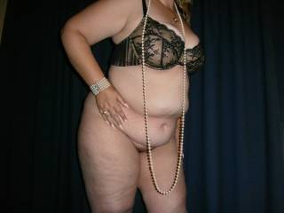 A black bra and pearls, perfect attire for the night ahead.
