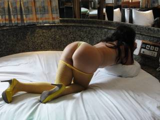in yellow high heels in panties and fishnets.