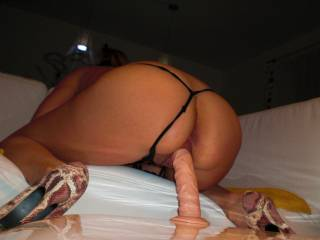 Very hot pic of this hottie riding that toy.  Great view of it entering her beautiful pussy.  We love the g-string pulled to the side and her wearing those sexy CFM heels as she plays.  Awesome pic.