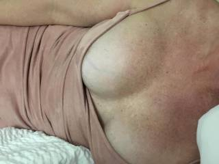 Picture of my slut\'s tits about to break out of her top while she\'s in resting.