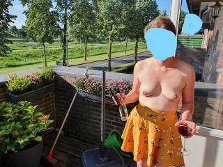 Since the weather was great where we live, my wife descided drop her top and wear only her skirt and panties on our balcony. At one point she presented herself standing full upright, and everybody could see her beautiful tits!
