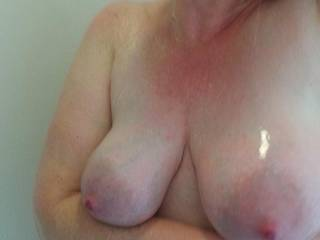 Heavy milk filled tits propped up in the shower