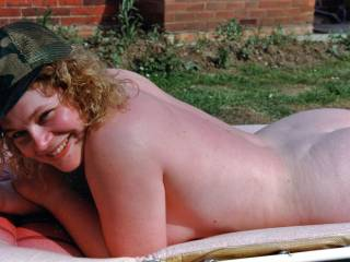 A cute chubby girl sunbathing nude and smiling