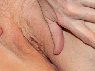 Rubbing around that hot looking pussy.  Stimulates me, how about you?
