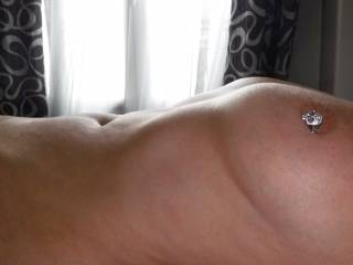 The morning sun shining on my new blingy nipple piercing, at the swinger hotel in Cap D'Agde, where we have just been on holiday.