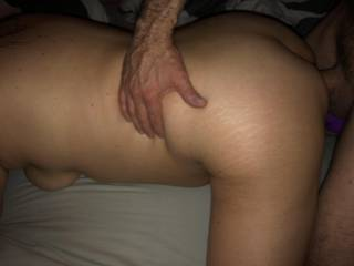 He takes a good grip on her ass, fucks her anally while she has a dildo in her tight cunt