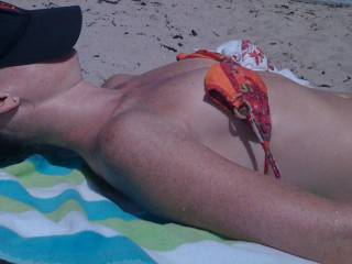 Her tits are tiny, perky and perfect on the beach.