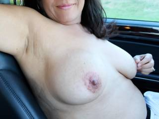 Out for a drive to take photos.  It started with me simply driving with my tits out of my top, but turned into me slowly getting fully naked.  Here I am topless in my car...behind the wheel pinching my nipple.