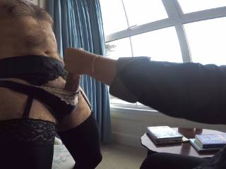 Hubby likes to wear wife\'s lingerie, stockings, suspenders and sexy panties while she gives him a handjob in the hotel window