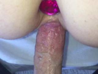 Sliding it in her hot pussy while looking at her ass plug.  So damn hot!