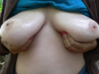 One more from my favourites. Outdoors in woodland, sunny day, coat open, top up, tits out, tits oiled, tits held up, orange nail varnish. A nice display