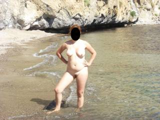 showing off her gorgeous tits and curvy naked body on the beach