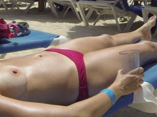 """She should have used one of those super-tiny """"wicked weasel"""" thongs to impress people around as she barely covers her slit and shows most of her crotch around. Her tits look delicious all exposed for others to see and watch her."""