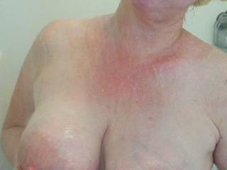 Propping up her heavy milk filled tits in the shower