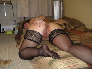 Preparing to be licked with her pussy and butt in in the air in black stockings.