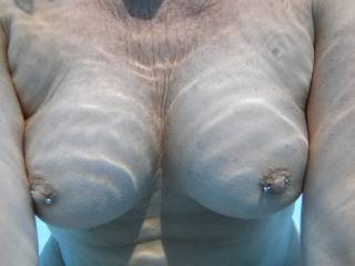 My pierced nipples and big tits underwater in our swimming pool at home.