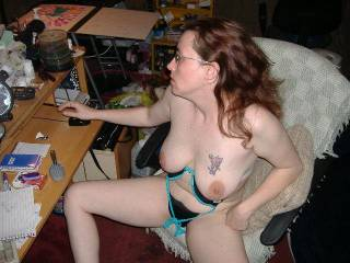 I love how she's sitting with her legs spread wide & her big tits hanging out.  She is a real turn on. Nice tit tatt too!