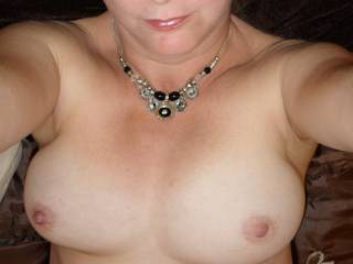 This is a classy, sexy pic.  Love the boobs.  They look ready to be licked and sucked.  What I also notice is the necklace. That with the lipstick, and the dainty, yet inviting mouth.  This woman has intense passion and will rock your world.