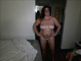 Wife posing for a picture in a hotel after playing with a lover