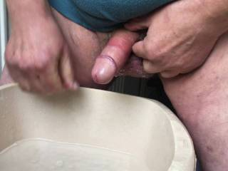 I made seven videos this morning - after this first one I then made five with wanking in each part of the house then the last was on the back of a chair. Here is a bowl of water on a stool, and I am washing my cock and long foreskin