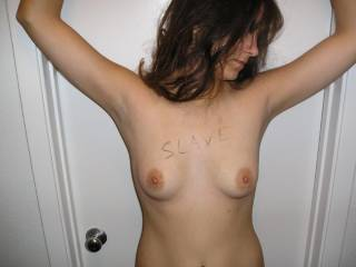 My submissive sex slave gf with wrists tied to the door jam over her head. The words SLAVE are written in block letters on her chest to claim her for my own. This is exactly what she wants, to feel completely owned by her master, at least for this day. Of