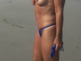 Walking topless on the beach.