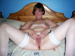Mature wife poses on her bed wearing only her fishnet stockings and spreading her thighs wide to display her perfect pussy.