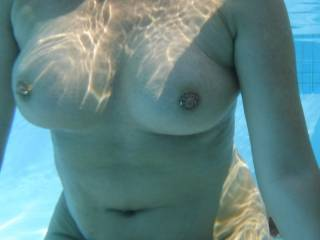 Underwater view of my tits with their pierced nipples, in our swimming pool at home.