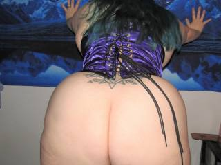 My wife showing off her wide hips and ass from behind in her new corset.