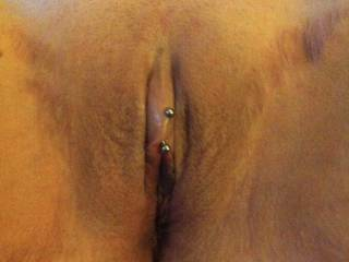 Close up of the wife's bald pussy and pierced clit.