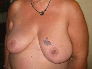 view of fher big pierced and tattoos tits