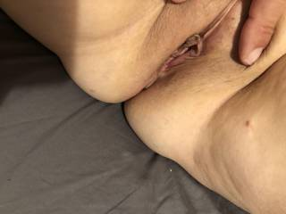 Opening up her freshly shaved sweet mature pussy.