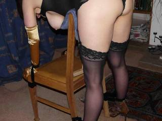 Love those Gold, Fuck me heels. and Black, lace top stocking are very effective.  I love being strapped in positions like that, and used.  Somebody quick, slip those panties over to the side, and slam a dick into her.