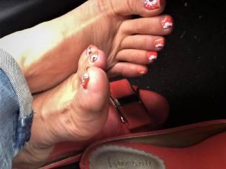 Ouk posing her  feet and orange deisned pattern toenails ..