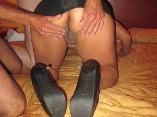 She\'s bent over starting to suck a dick while they paw at her ass and open her up
