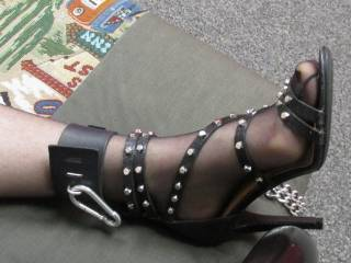 Another view of her lovely foot strapped in a hot heel and cuffed to the bed.