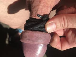 Tied cock head tight with lace to keep it enlarged